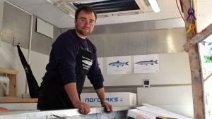 Anders Lindqvist står bakom en disk och säljer fisk.