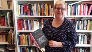 Maria Österlund poserar med boken Flicktion i handen.