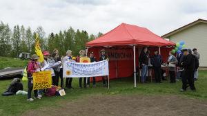 Kärnkraftsmotståndare från Sverige med plakat och flaggor på Parhalahtidagen, står bredvid Fennovoimas tält