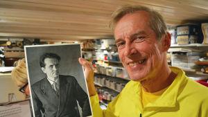 Eddie Bruce med en bild på Aatos Åkerblom.