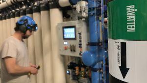 Tekniker intill monitor i ett vattenreningsverk.