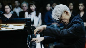 Ryuichi Sakamoto soittaa pianoa New Yorkin Park Avenue Armoryssa. Kuva async-konserttielokuvasta.