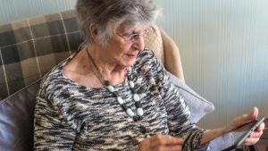 En äldre kvinna använder en surfplatta.