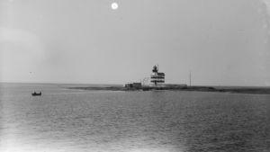 Vanha, mustavalkoinen kuva Märketin majakasta: Raidallinen majakka pienellä saarella, pieni soutuvene menossa saarelle tai tulossa sieltä pois.