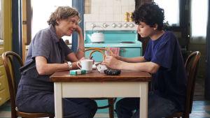 Äiti Dorothea (Annette Bening) ja poika Jamie (Lucas Jade Zumann) istuvat keittiön pöydän ääressä elokuvassa Vuosisadan naiset