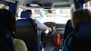 En chaufför kör en minibuss och två personer åker med.