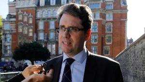 En man som bär glasögon och kostym intervjuas utomhus i stadsmiljö. Eliot Higgins grundade den undersökande gruppen Bellingcat.