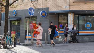 Kadulla kävelee nainen ja mies, jotka kantavat suuria pehmoleluja. Taustalla kävelee myös pariskunta, joilla lastenvaunut.