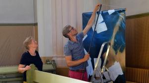 Ilar Gunilla Perssons fotografier hängs upp i Lovisa kyrka
