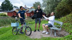 Pojkarna är vid ån, en av dem står med en gammal cykel, den andra skrattar och den tredje sitter på en bänk och gestikulerar.