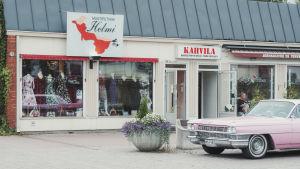 Klädaffären Muotiputiikki Helmi i Somero. Utanför står en pink Cadillac från 1964 parkerad.