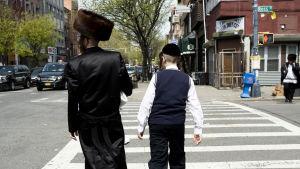 Äldre judisk man med pälshatt går över gata tillsammans med yngre i New York.