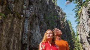 Nainen ja mies katselevat ylös korkean rotkon pohjalla. Yläpuolella kohoavat jyrkät kalliot ja taustalla näkyy puita ja taivasta.
