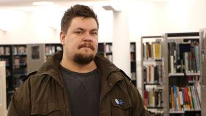 Mathias Rosenlund med brun jacka i ett bibliotek, tittande rakt in i kameran.