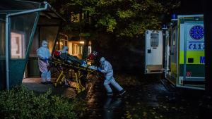 Ett ungerskt ambulansmanskap förflyttar en coronapatient från intensivavdelningen på ett sjukhus i Budapest till ambulansen.