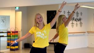 En flicka står framför spegeln i en danssal med armarna utsträckta. Hon ler och har på sig en gul t-skjorta med texten Hurja Piruetti.