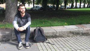 Litauenpolacken Lukaš Mikelevič sitter på trottoarkanten.