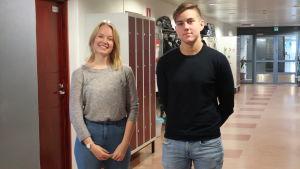 En ung man och kvinna står i en skolkorridor.