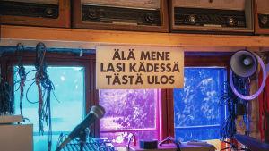Kyltti jossa teksti Älä mene lasi kädessä tästä ulos, kiinnitetty ikkunaan, ympärillä mikrofoni, piuhoja, miksauspöytä, yms. tavaraa.