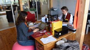 Olga och Tuukka Temonen sitter mittemot varandra vid ett stort skrivbord och arbetar.