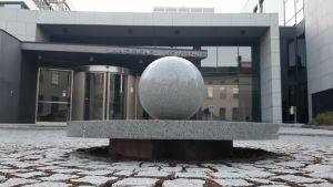 Ett stort grått stenklot pryder innergården framför glasdörrarna till Egentliga Finlands tingsrätt i Åbo.