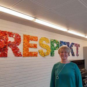 Rektor Catharina Sunesdotter står framför en bild med texten respekt i skolans korridor.