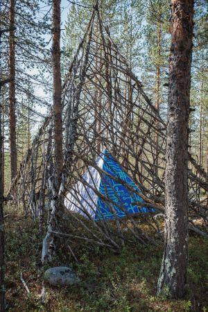 Sinisävyinen pyramidinmuotoinen veistos, puinen kehikko ympärillä