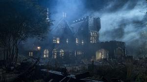 Ett gammal spöklikt hus i månsken och dimma.