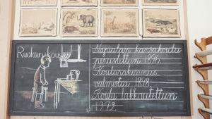 """Musta kirjoitustaulu jossa liidulla kirjoitettun teksti: """"Napialan kansakoulu perustettiin vuonna 1896. Koulurakennus valmistui 1898. Koulu lakkautettuun 1972."""""""