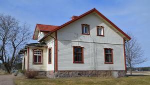 Ett vitt gammalt hus med röda knutar.