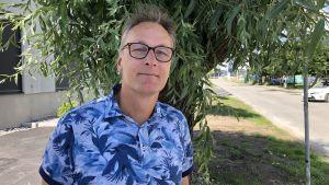 Fredrik Nilsson står i en blå skjorta utomhus.