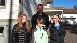Rektor och tre elever framför skolbyggnaden