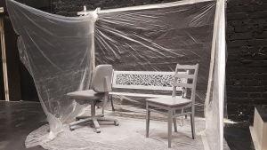 Scenografin i pjäsen Raseborgs ruiner. Bänkarna och stolarna är målade gråa.