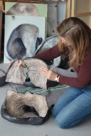 Bildkonstnären Magdalena Åberg håller upp bitarna till ett konstverk i keramik som spruckit