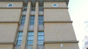 Den svagt gula fasaden på Rettigska huset med smårutiga fönster och dekorationer under fönstren.