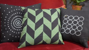 Kolme käsintehdyt tyynyt sohvalla