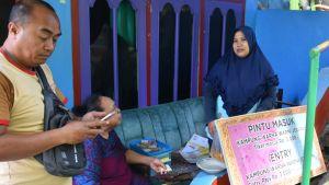 Man betalar inträdesavgift vid ingången till en slum i Malang, Indonesien