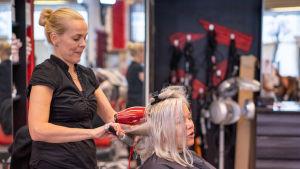 Parturi-kampaaja Minna Budde föönaa asiakkaan hiuksia.