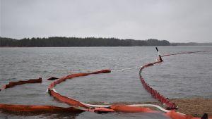 Röda bommar som ska hindra oljan från att sprida sig i vattnet. De vita bommarna suger upp oljan.