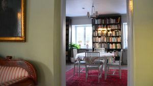 På bilden synns ett bord och stolar samt en bokhylla medböcker. Bilden är tagen från dörröppningen i ett rum med gröna väggar in mot biblioteket.