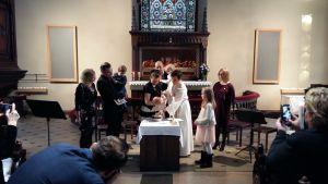 Föräldrar, gudföräldrar och barn står runt en präst som döper ett barn i en kyrka.