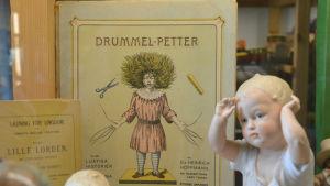En sagobok om Drummelpetter inuti ett vitrinskåp.