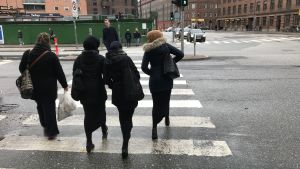 Unga damer i niqab och lång kjol går över övergångsställe.