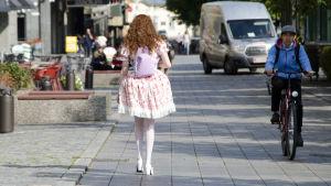 En kvinna klädd i så kallade Lolitakläder - en fluffig vit och rosa klänning med spetsar på. Hon har vita högklackade skor, blommor i håret och en lila ryggsäck med kaninöron på. Vi ser henne bakifrån när hon går på en trottoar i centrum av Vasa.