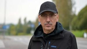 En äldre man med glasögon och keps på huvudet. Står utomhus och tittar in i kameran.
