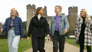 Au pairit Irlannissa sarjan henkilöt Ada, Luna, Igi ja Nea hymyilevät.ja kävelevät hiekkakäytävällä takanaan linna.