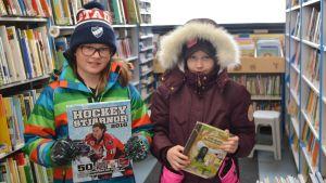 två elever från Gammelbacka skola lånar böker i bokbussen.