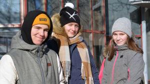 Julian Kevin, Viivi Tasanko och Elin Westerlund står ute med vinterjackor och mössor på.