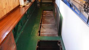 En septiktank är synlig under golvet i en båt när luckan har lyfts upp.