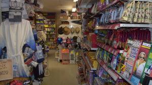 En smal gång i en butik. Mycket varor, bland annat tidningar, godis och kläder på båda sidor av gången.